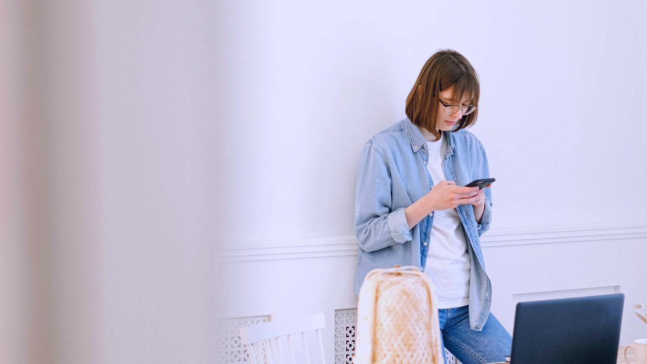 Mulher olhando celular. Imagem remete à visualização da atualização da versão do TISS.
