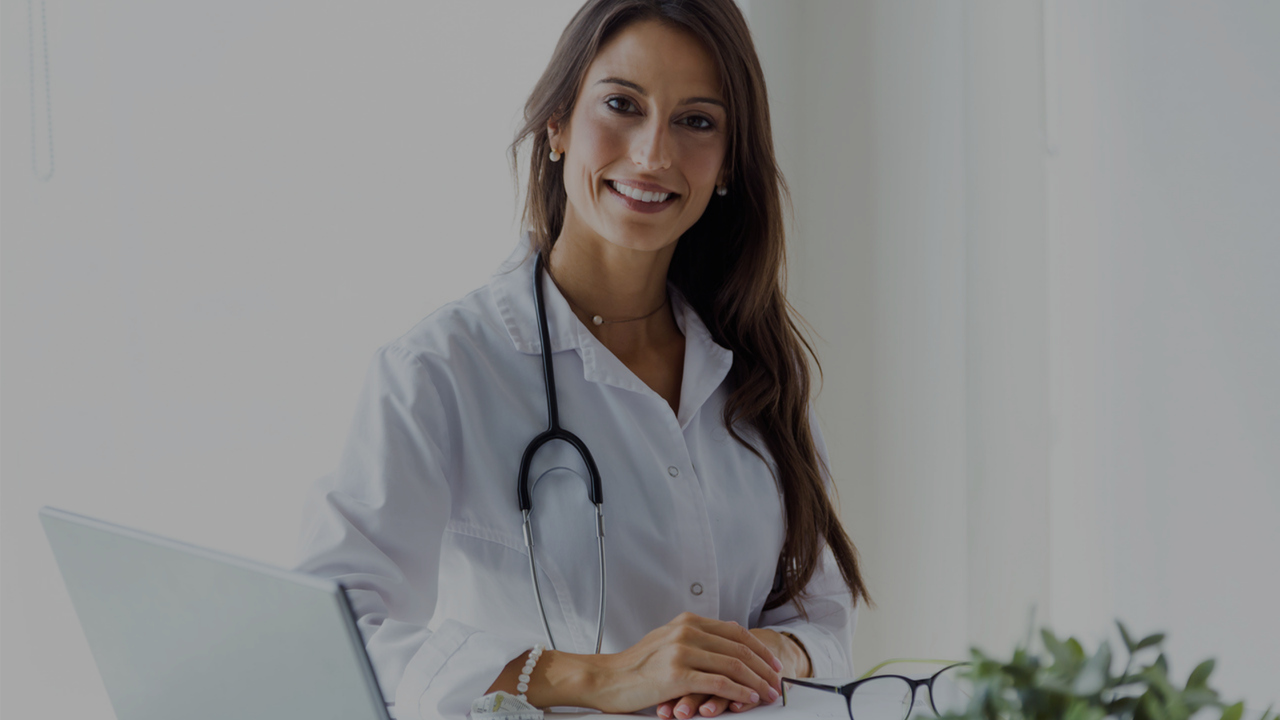 Médica em frente ao computador. Imagem simboliza a saúde suplementar, e a diferença entre tiss e tuss.