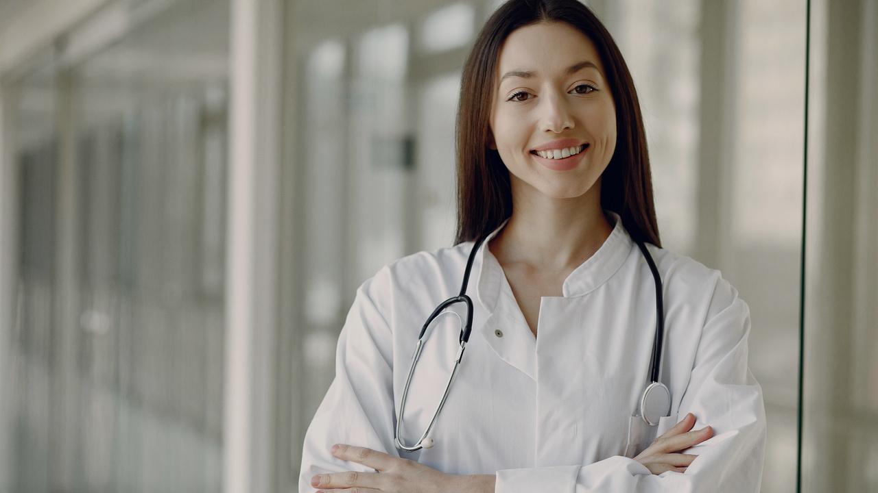 Médica sorrindo. Imagem simboliza profissional feliz por conseguir definir o preço das consultas.