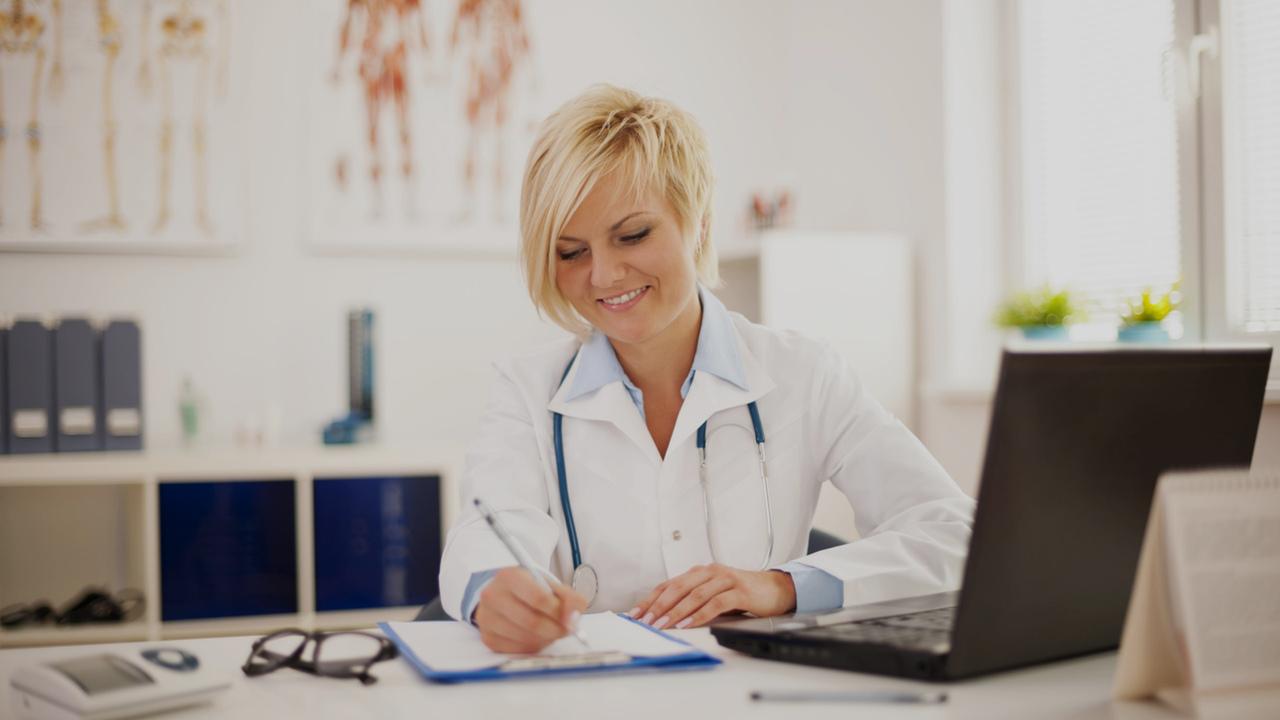 Médica trabalhando em sua sala, atuando por meio da Telemedicina.