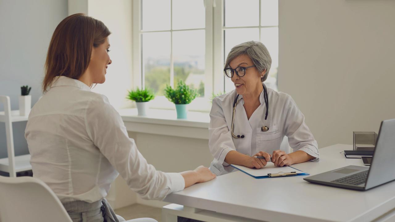 Médica conversando com paciente. Imagem remete à organização de consultório médico.