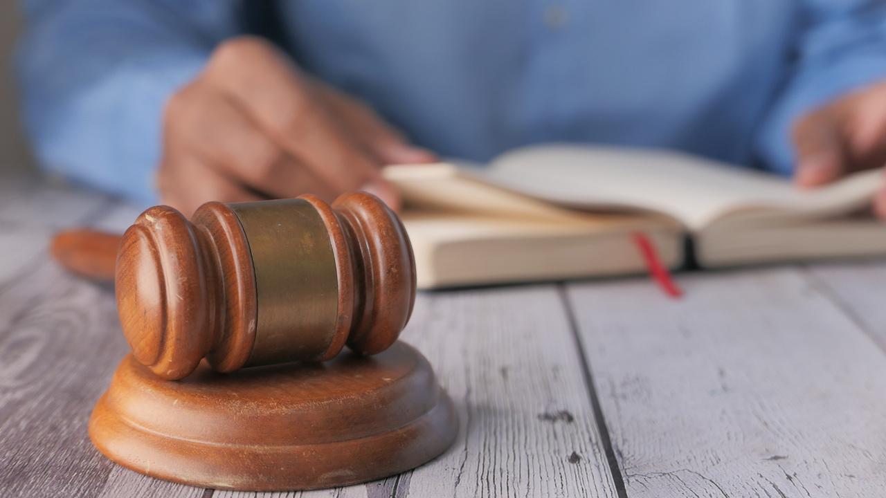 Martelo da justiça e livro de legislação. Imagem simboliza a lei 14.063.