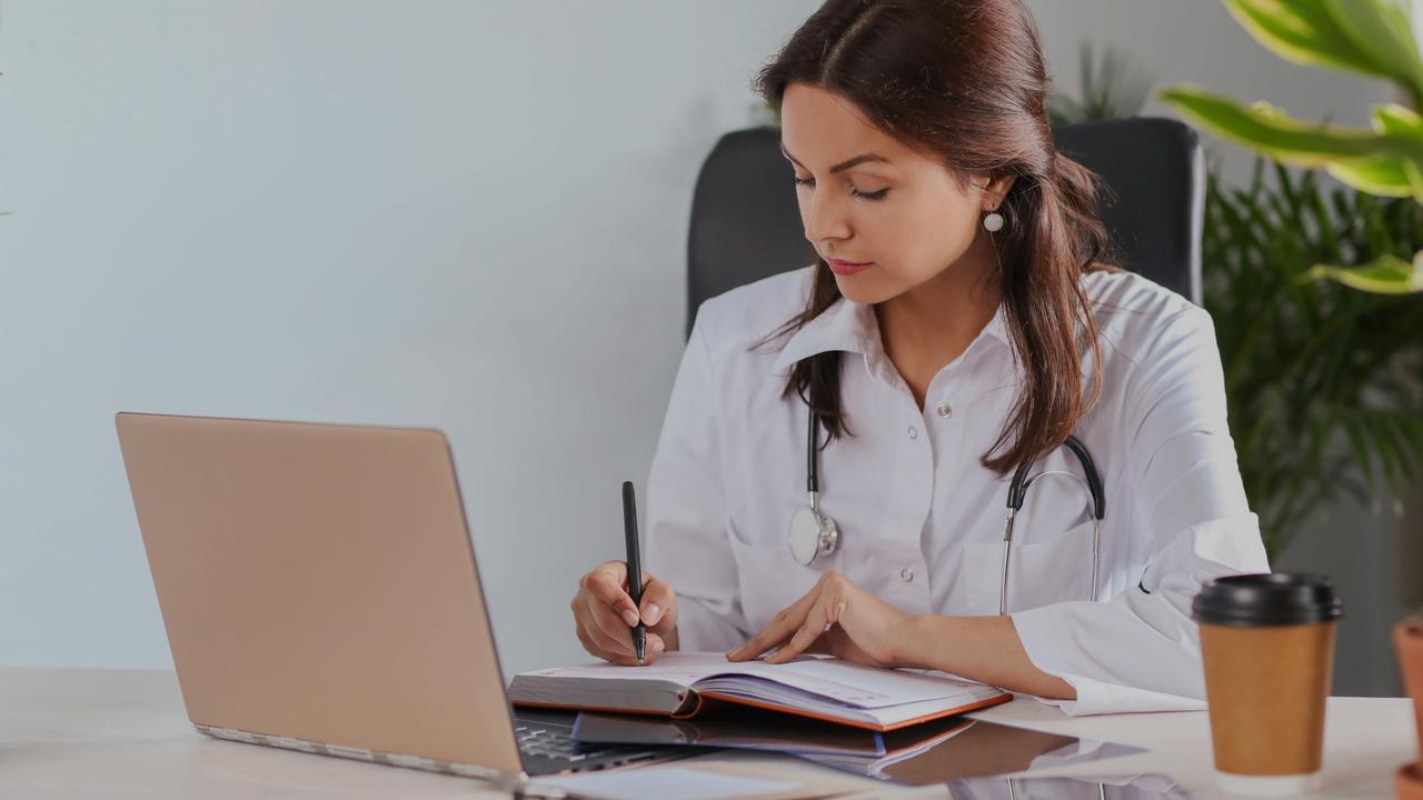 Médica fazendo anotações. Imagem simboliza profissional trabalhando com o padrão TISS.