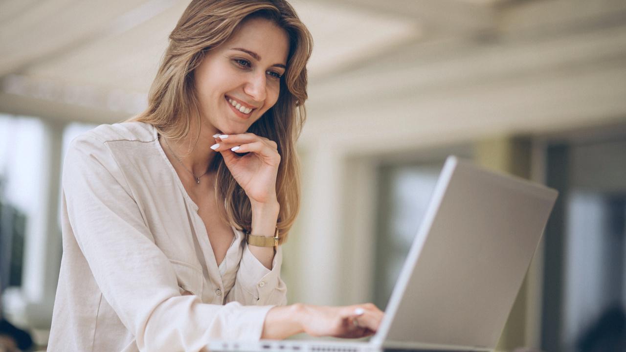 Profissional sorrindo em frente ao computador. Imagem simboliza profissional mexendo na área do cliente do Validador TISS.