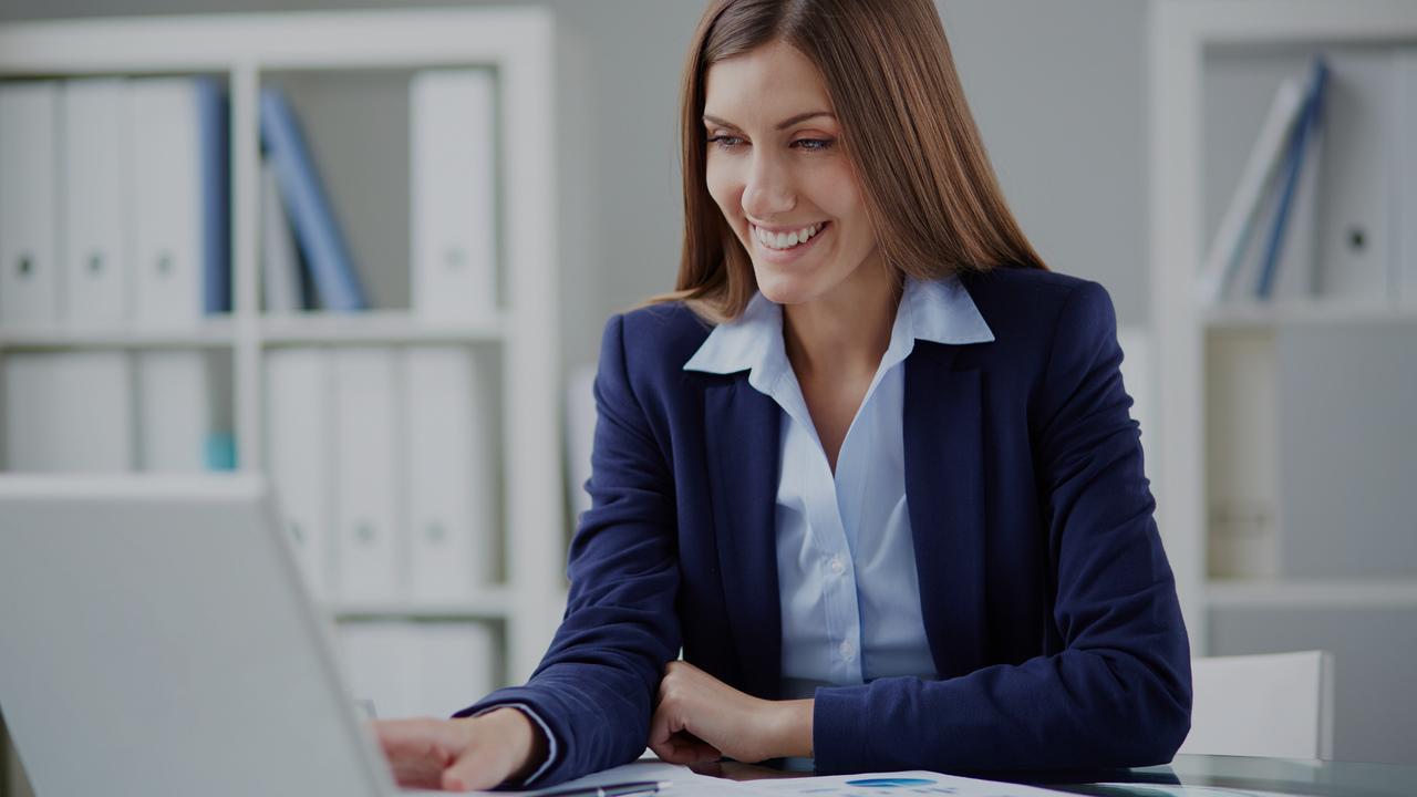 Profissional olhando para a tela do computador. Imagem simboliza faturista olhando os termos comuns do setor de faturamento hospitalar.