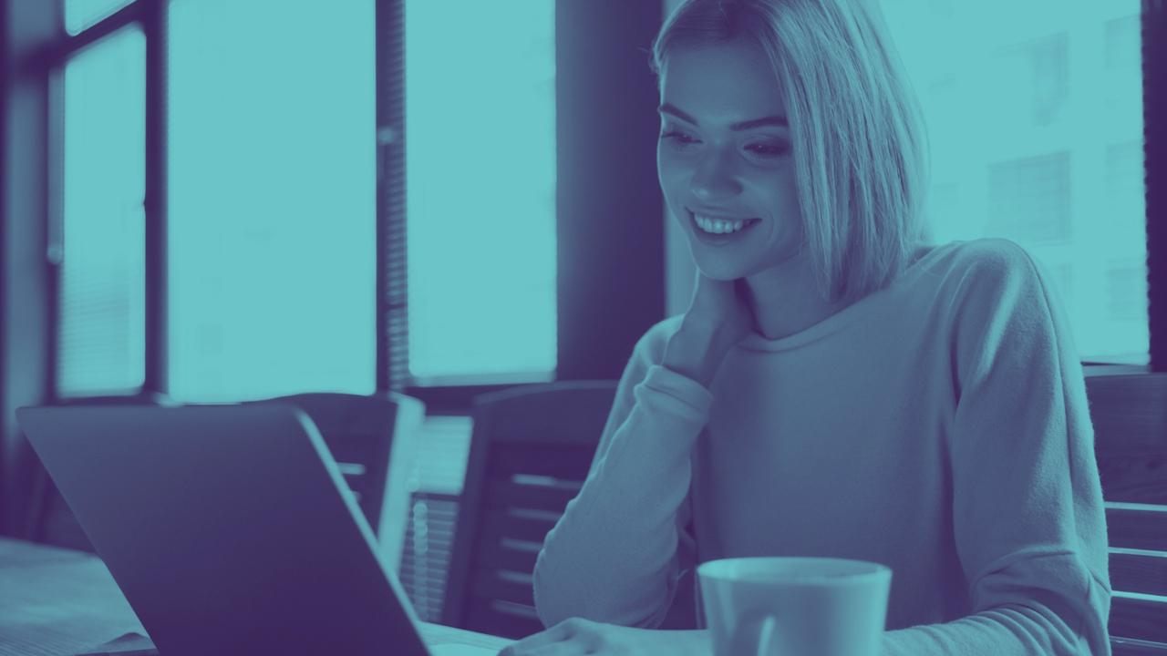 Profissional sorrindo olhando para computador. Imagem representa profissional fazendo o envio do XML TISS.