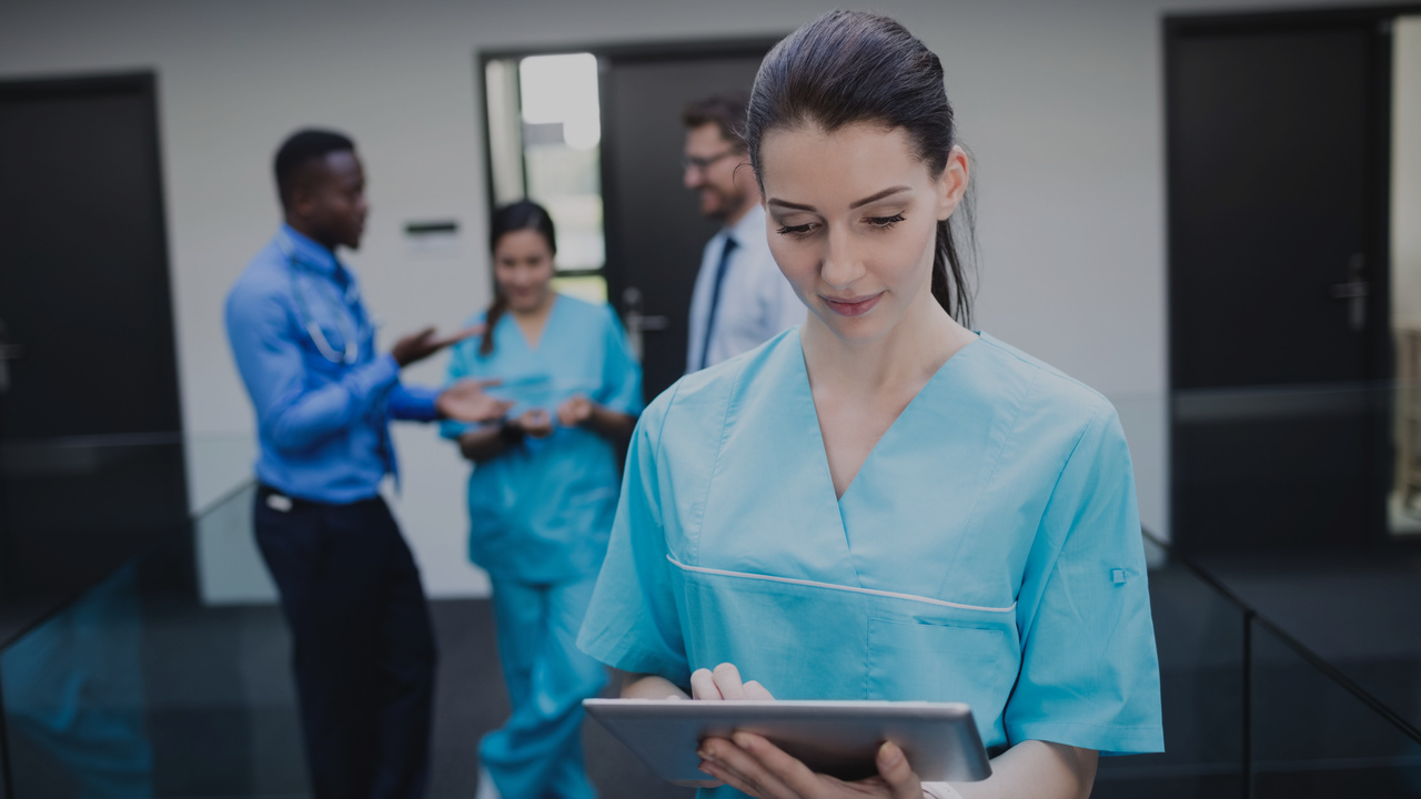 Médica segurando tablet e equipe conversando atrás dela. Imagem representa que o time pretende modernizar o consultório.