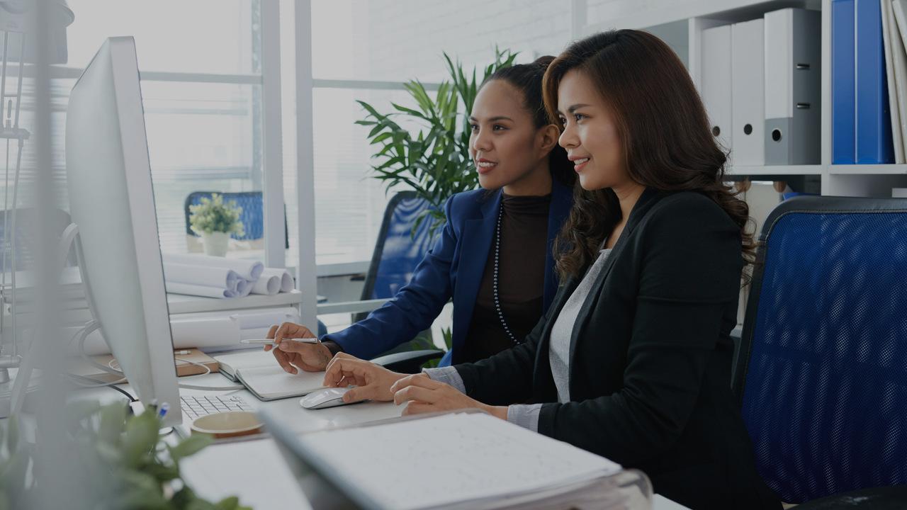 Duas profissionais olhando para o computador. Imagem simboliza profissionais do setor de faturamento vendo os benefícios do Validador TISS.