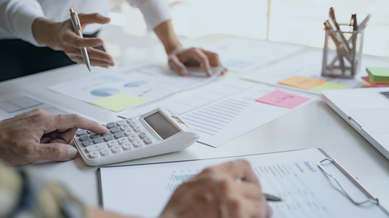 Profissionais trabalhando com papéis e calculadora em cima da mesa. Imagem simboliza a auditoria de contas médicas.