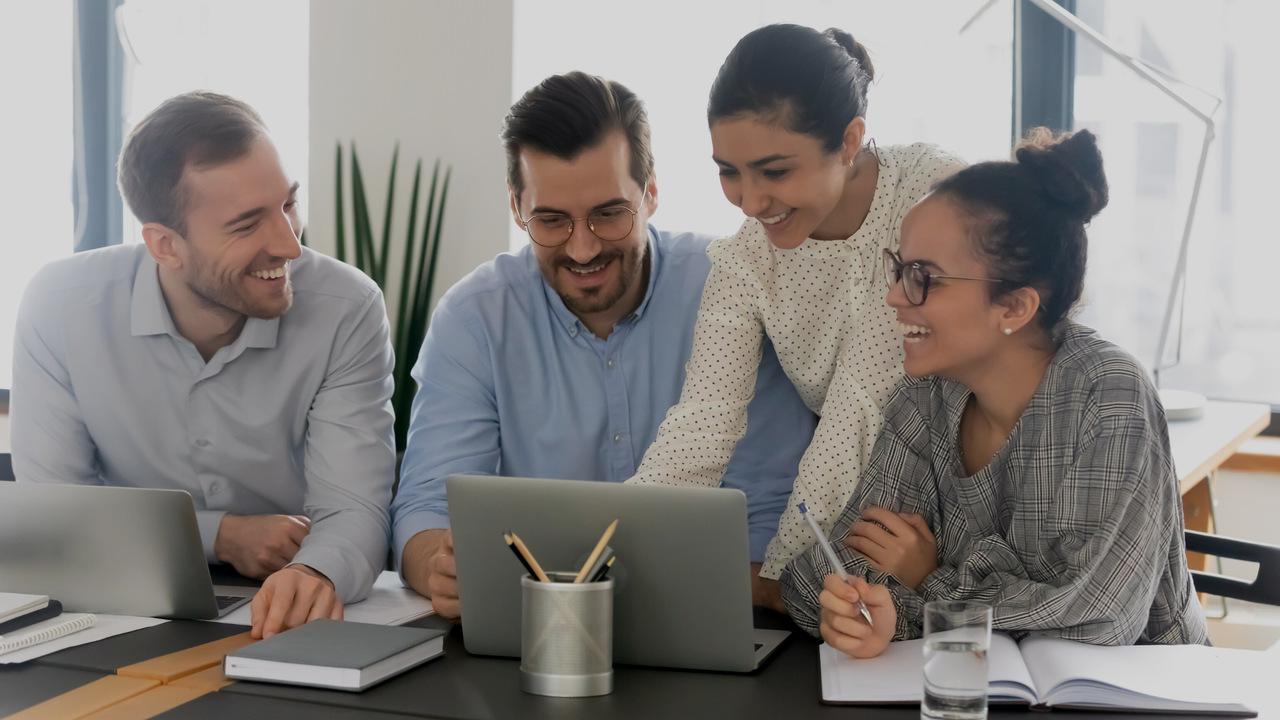 Quatro profissionais sorrindo em frente ao computador. Imagem simboliza que os profissionais estão controlando as glosas médicas.