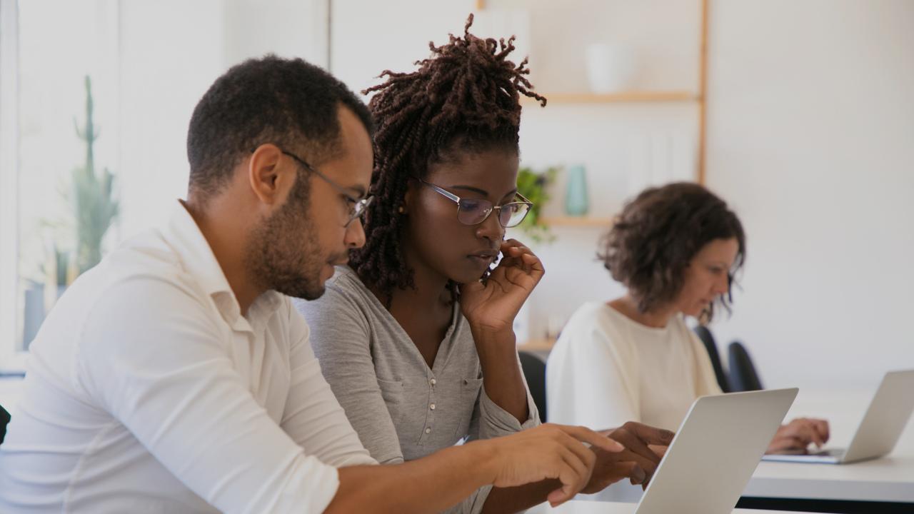Profissionais em frente ao computador. Imagem simboliza o faturamento hospitalar digital.