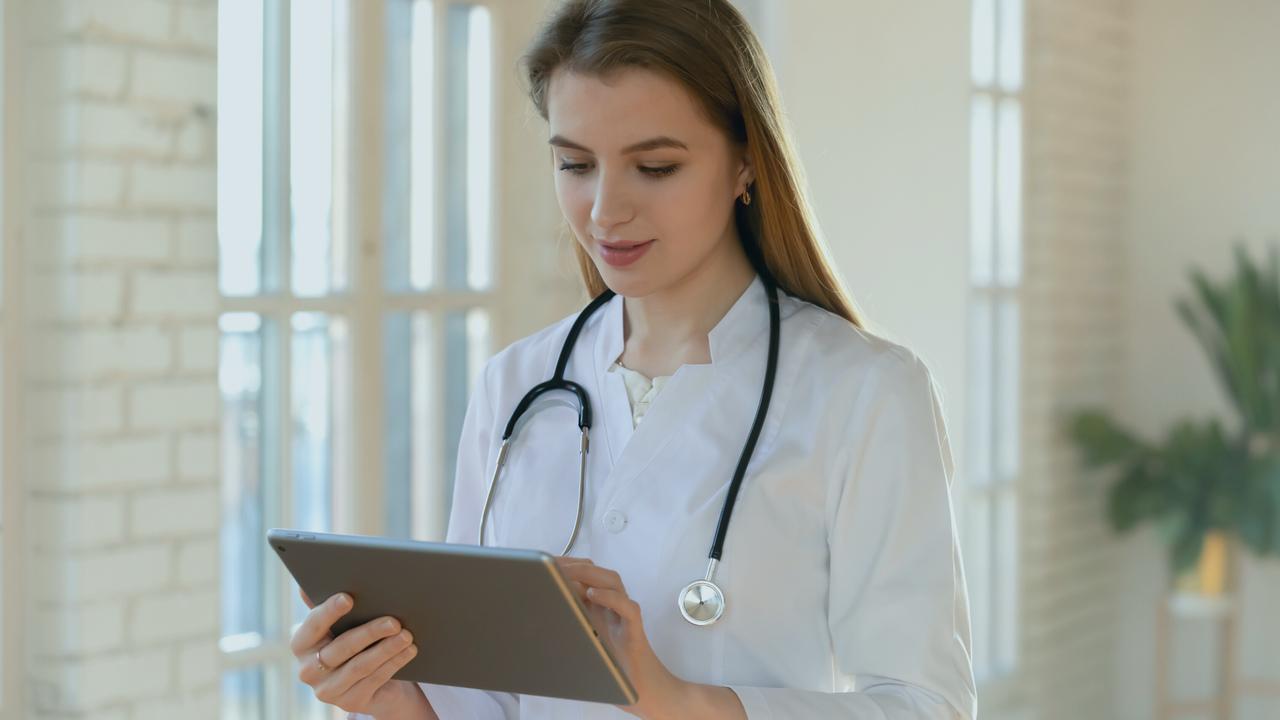 Médica segurando tablet. Imagem representa que a profissional está fazendo uma receita digital.