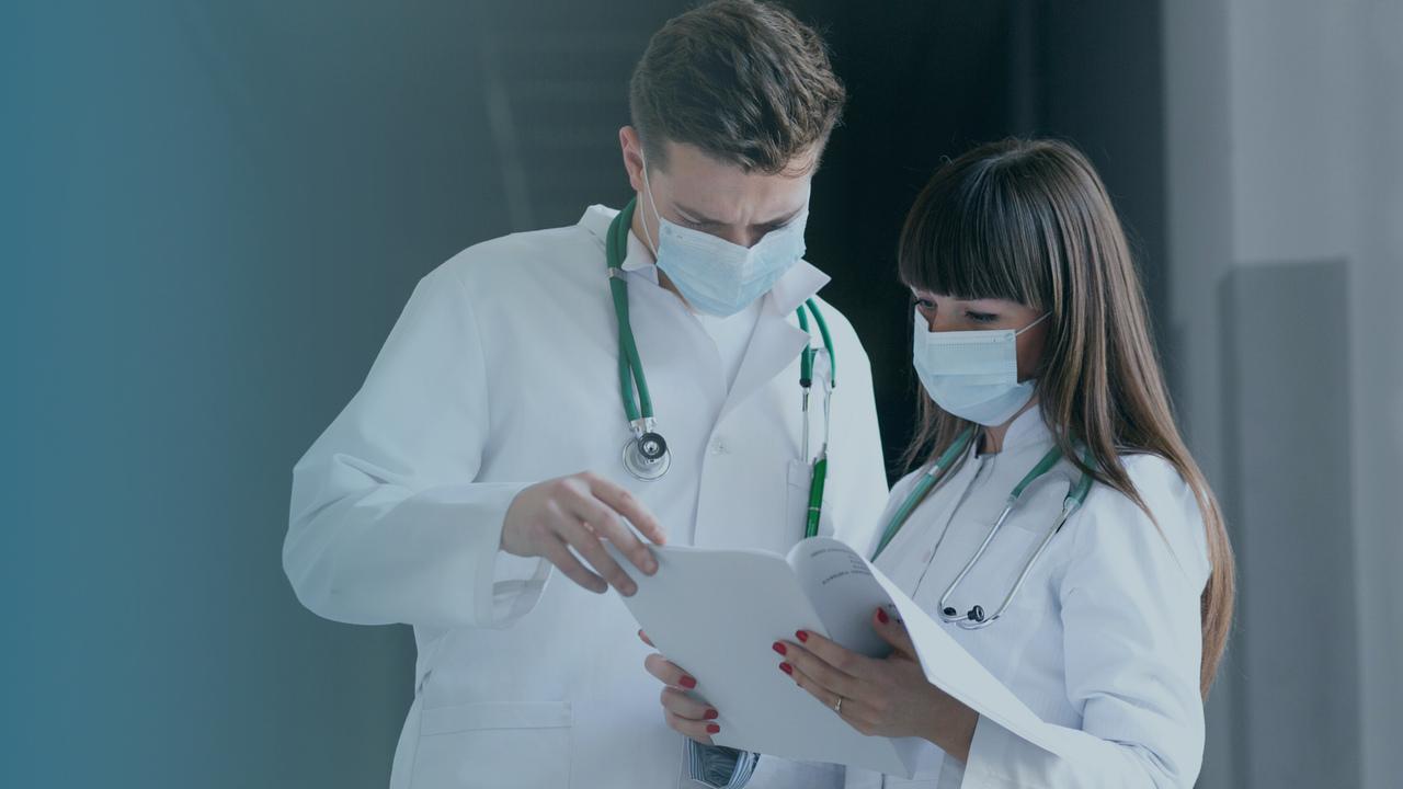 Dois médicos conversando. Imagem simboliza que estão falando sobre erros médicos que podem afetar o faturamento.