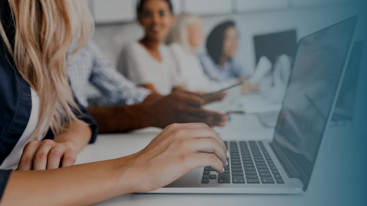 Equipe trabalhando em frente ao computador. Imagem simboliza funcionários da operadora trabalhado com o Monitoramento TISS.