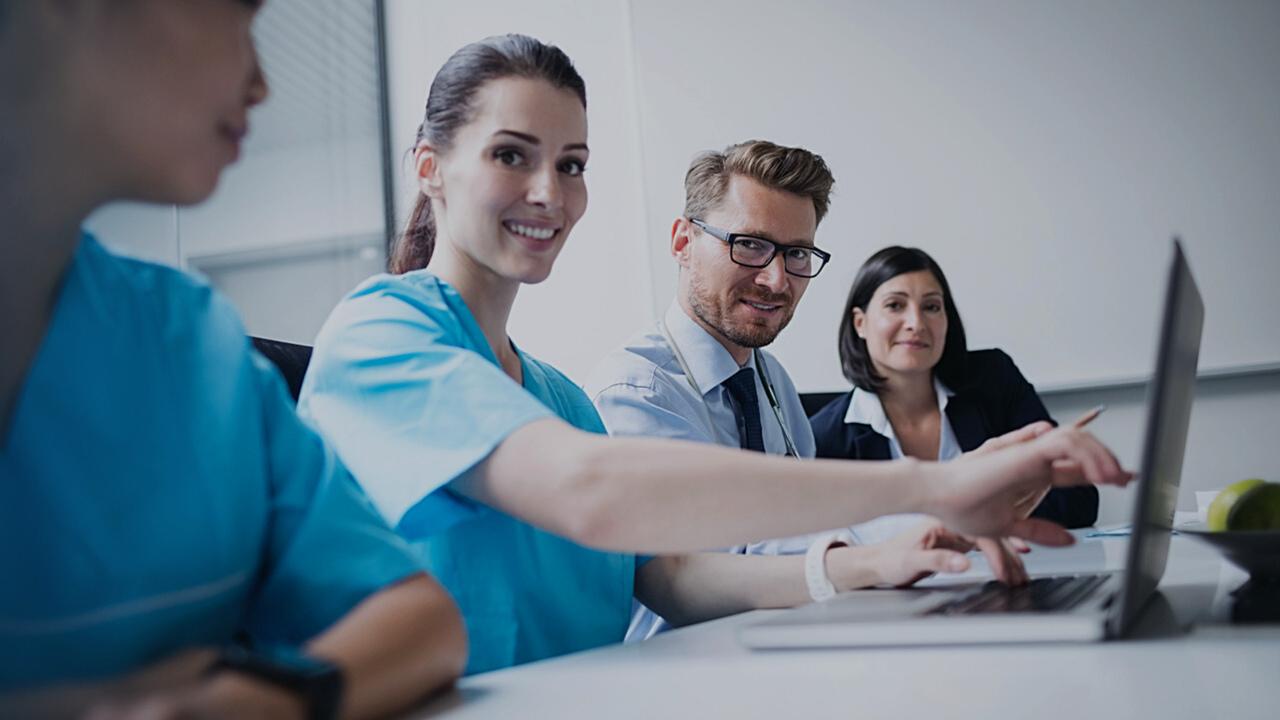 Profissionais de saúde trabalhando em frente ao computador. Imagem simboliza que estão gerenciando prestadores autorizados no Validador TISS.
