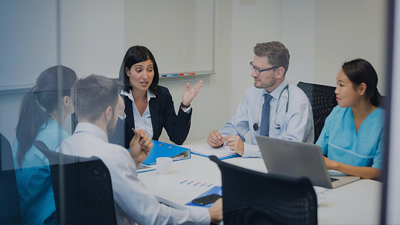 Profissionais de saúde e administrativos conversando. Imagem simboliza a discussão sobre os desafios atuais das operadoras de saúde.