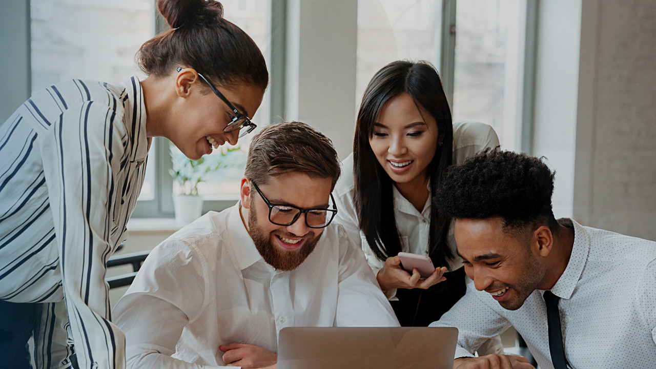 Quatro profissionais conversando em frente ao computador. Imagem simboliza que estão trabalhando com ferramentas de gestão para operadoras.