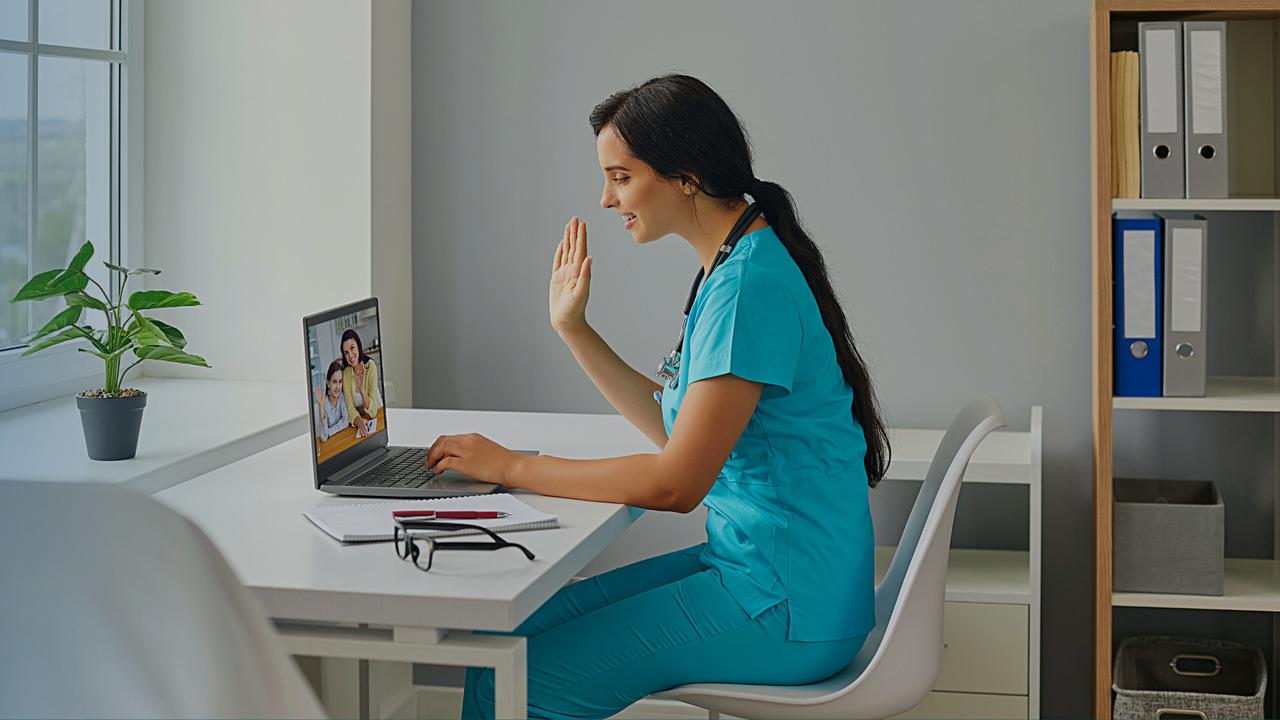 Profissional de saúde fazendo atendimento via computador. Imagem simboliza o cuidado com o paciente e zelo para reduzir inadimplência em clínicas.