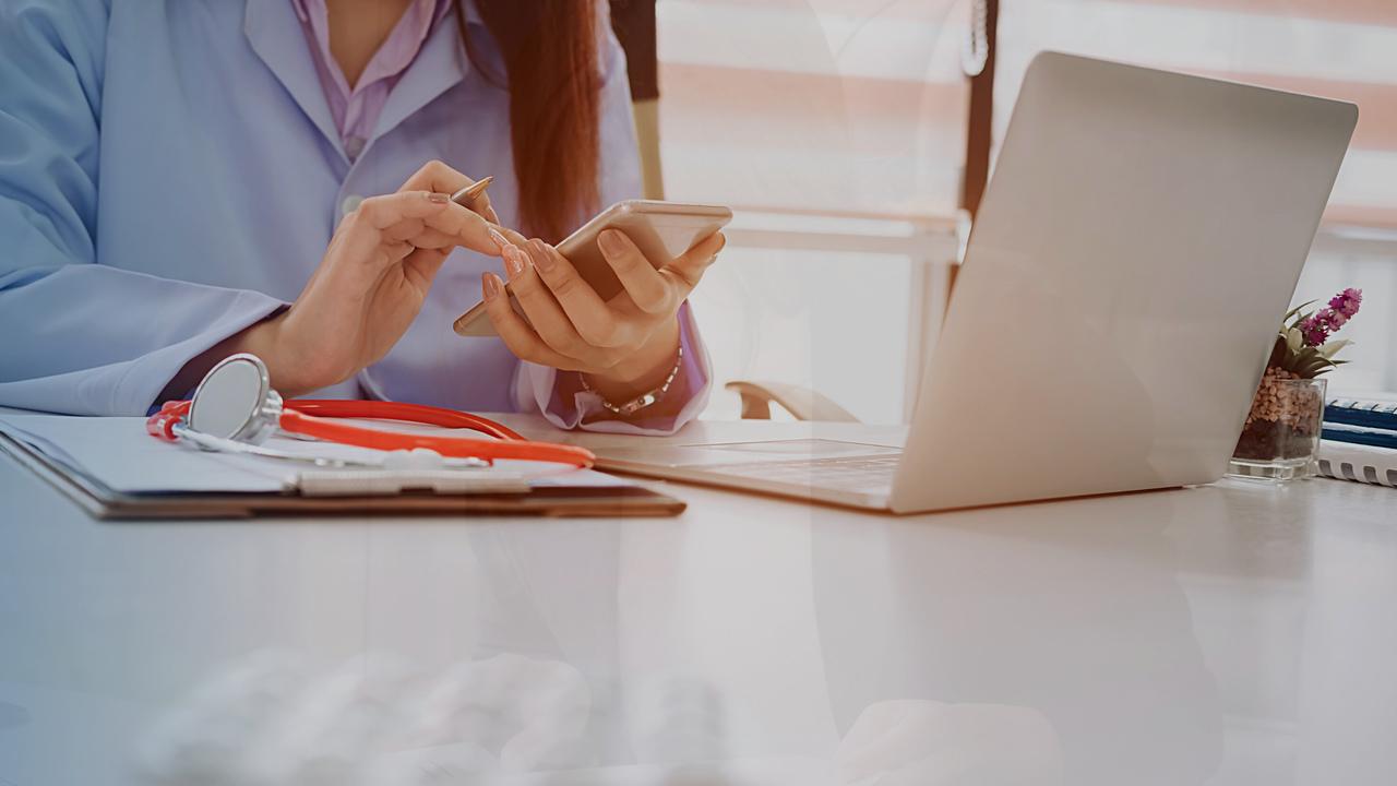 Médica mexendo no celular. Imagem simboliza que a profissional está pesquisando sobre a sinistralidade nas clínicas.