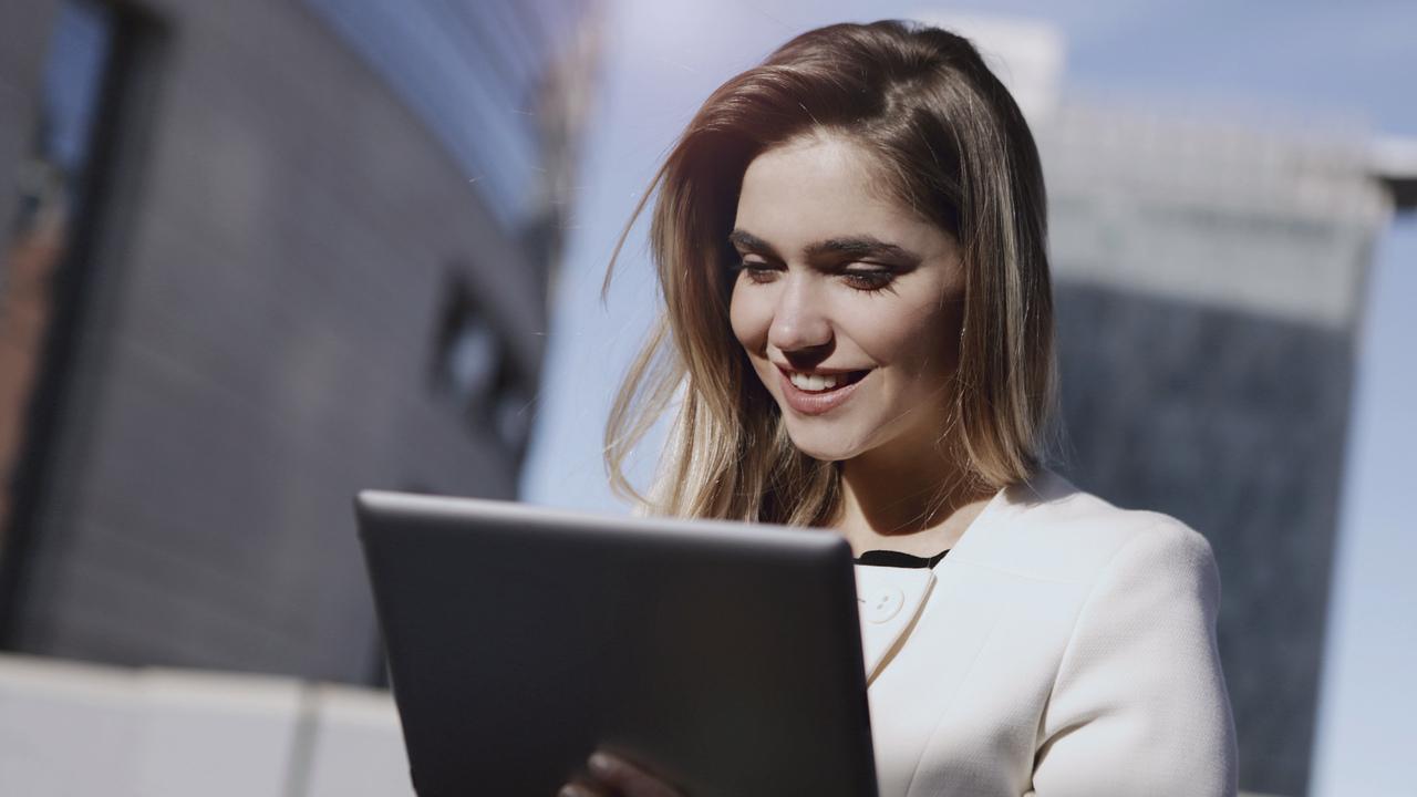 Mulher olhando tablet. Imagem simboliza o setor médico trabalhando com o certificado digital.