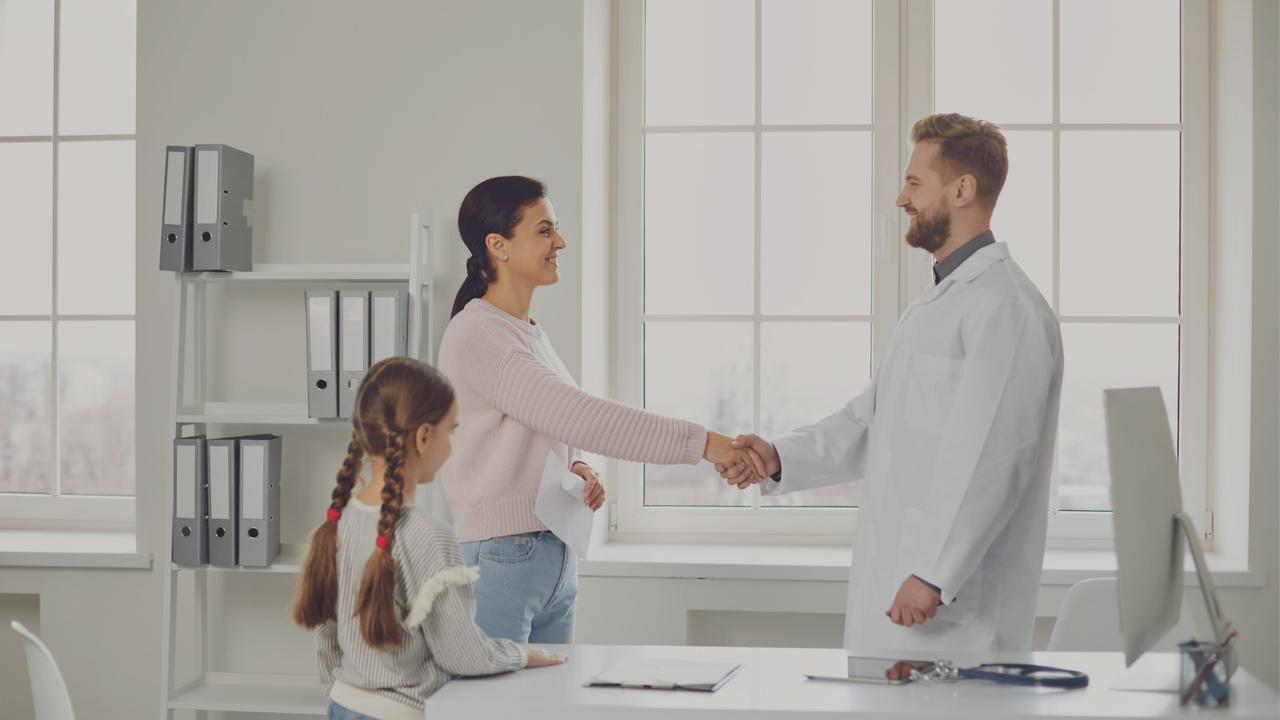 Médico apertando a mão da paciente em forma de cumprimento. Imagem representa que estão em um consultório.