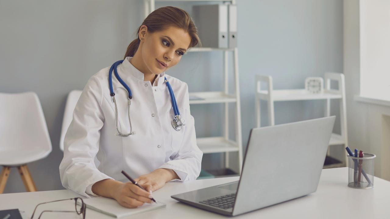 Médica olhando para o computador e escrevendo no bloco de notas. Imagem simboliza o trabalho com os documentos médicos.