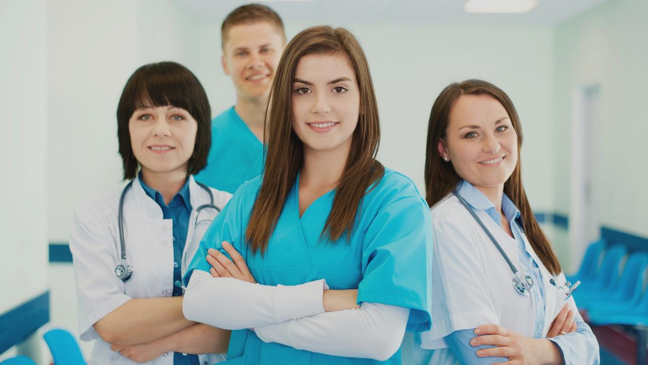 Equipe médica de 4 pessoas sorrindo. Imagem simboliza uma equipe médica empenhada.