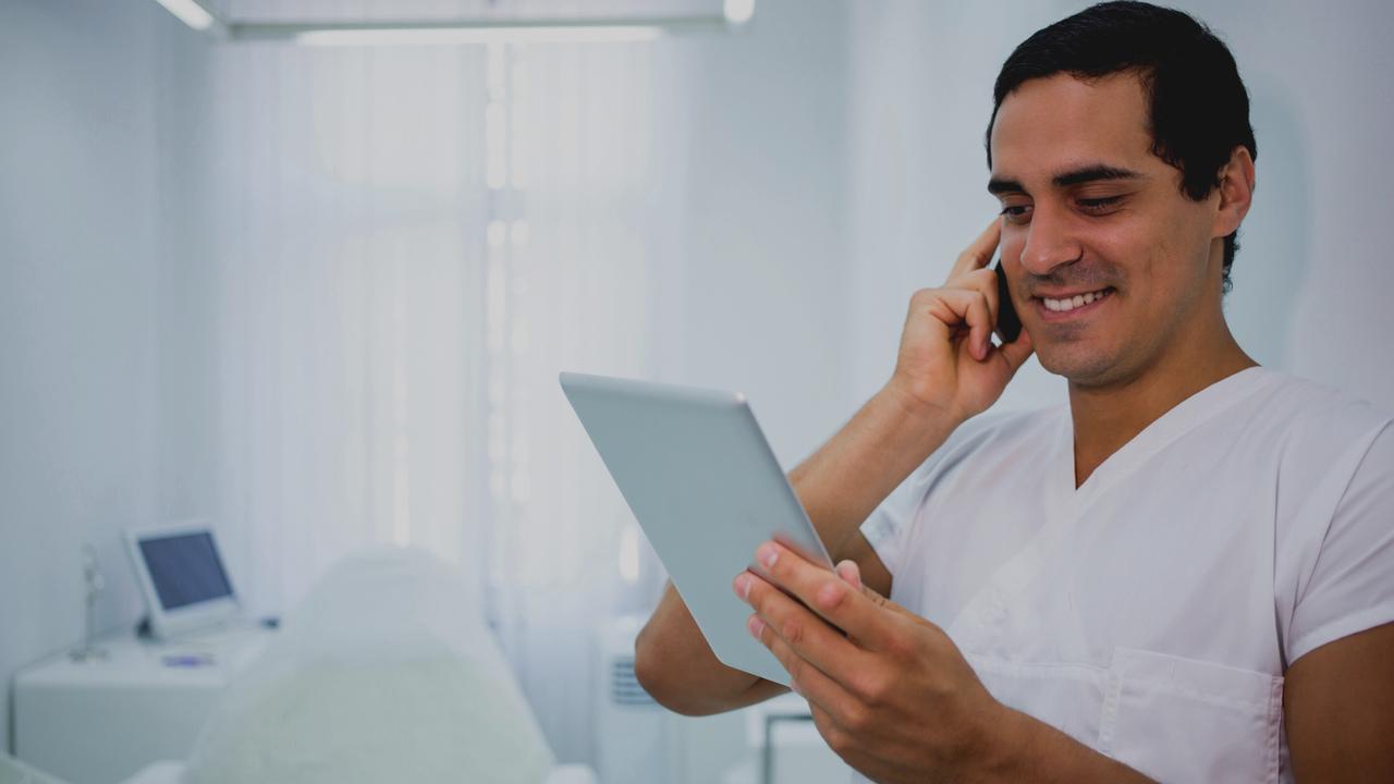 Médico com tablet na mão. Imagem simboliza que o médico está trabalhando com as guias médicas digitais.