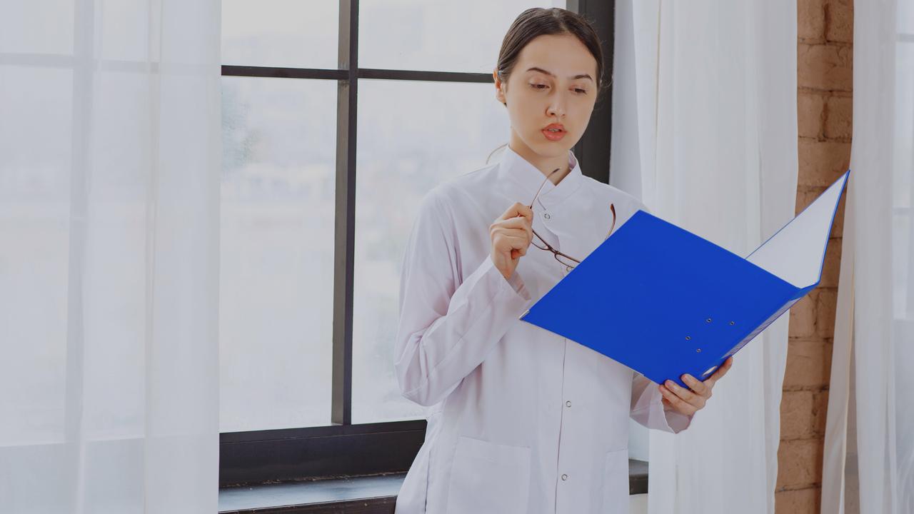 Fisioterapeuta olhando documento. Imagem simboliza que está revisando o faturamento de clínicas de fisioterapia.