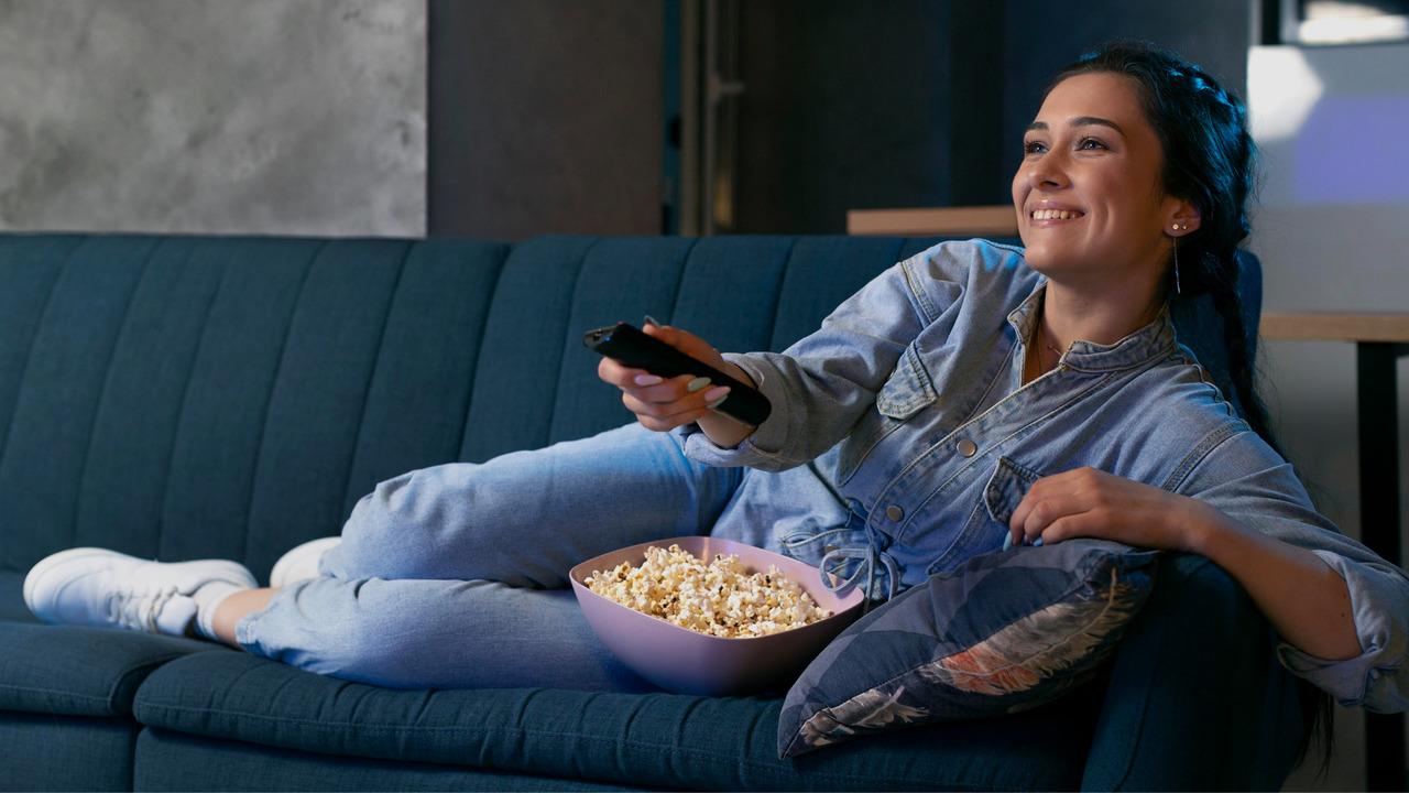 Mulher deitada no sofá, com pipoca no colo. Imagem simboliza que está procurando filmes de medicina para assistir.